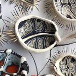 Image: Penny Evans, Estuarine Creatures with Gawu 2018, white earthenware with sgraffito and glazes, echidna quills, emu feathers, plastic flowers, raffia.